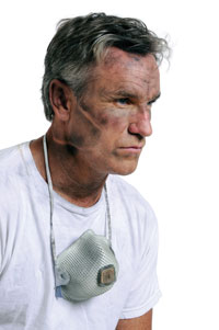 man with dirty face and respirator face mask around neck