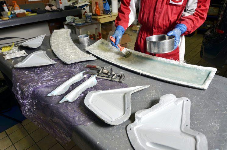 worker fabricating fiberglass car parts
